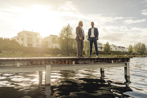 Two businessmen standing on jetty at a lake - KNSF03349
