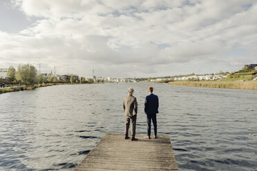 Two businessmen standing on jetty at a lake - KNSF03352