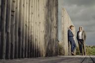 Two businessmen standing on boardwalk talking - KNSF03355