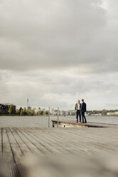 Two businessmen standing on jetty at a lake talking - KNSF03364