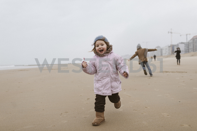 Happy little girl with lolly running on the beach in winter while her brother playing in the background - KMKF00097