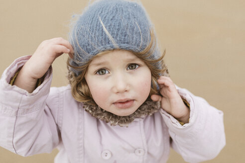 Portrait of unhappy little girl on the beach in winter - KMKF00100