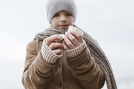 Boy's hands holding cuttlebone on the beach in winter - KMKF00103