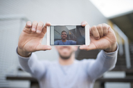 Smiling man taking selfie with cell phone, close-up - RAEF01958
