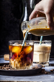 Hand pouring homemade vanilla flavoured coffee creamer into a glas with iced coffee - SBDF03424