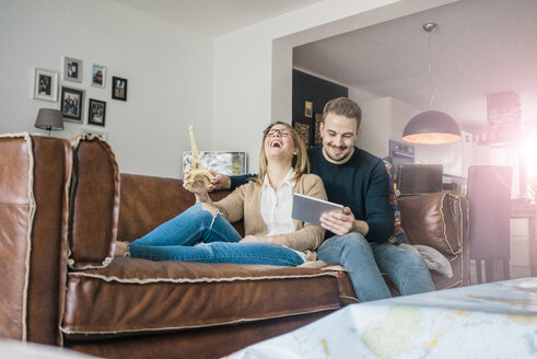 Happy couple sitting on couch at home with tablet and Eiffel tower model - MOEF00582