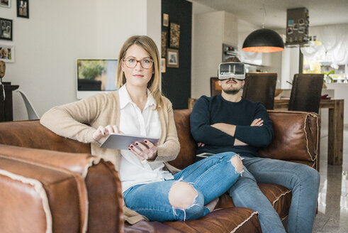 Couple sitting on couch at home with tablet and VR glasses - MOEF00585