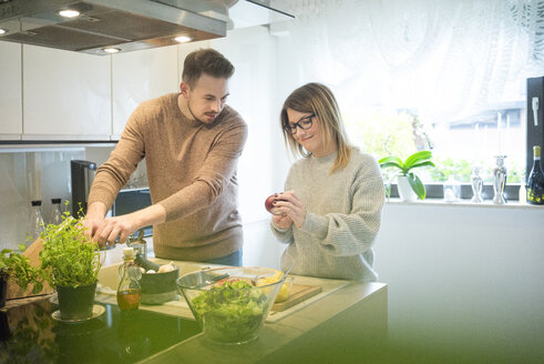 Couple preparing salad in kitchen together - MOEF00588