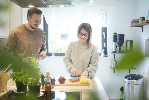 Happy couple preparing salad in kitchen together - MOEF00600