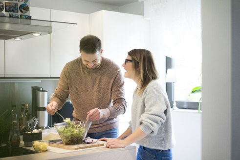 Happy couple preparing salad in kitchen together - MOEF00603