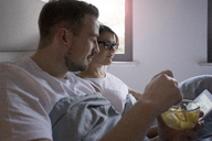 Couple in bed at home with snack and tablet - MOEF00609