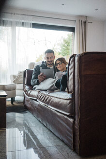 Smiling couple lying on couch at home sharing tablet - MOEF00624