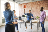 Colleagues playing basketball in office - HAPF02623