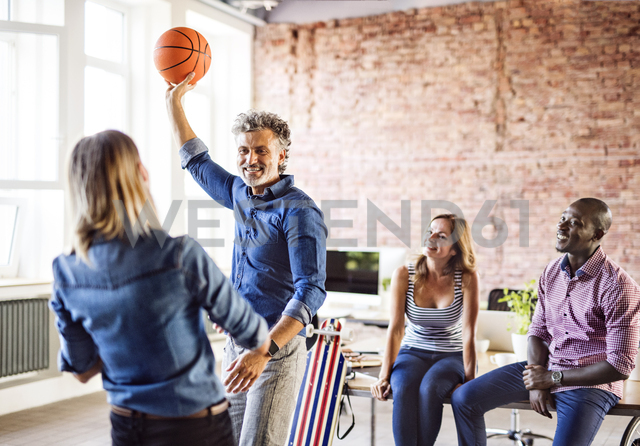 Colleagues playing basketball in office - HAPF02629