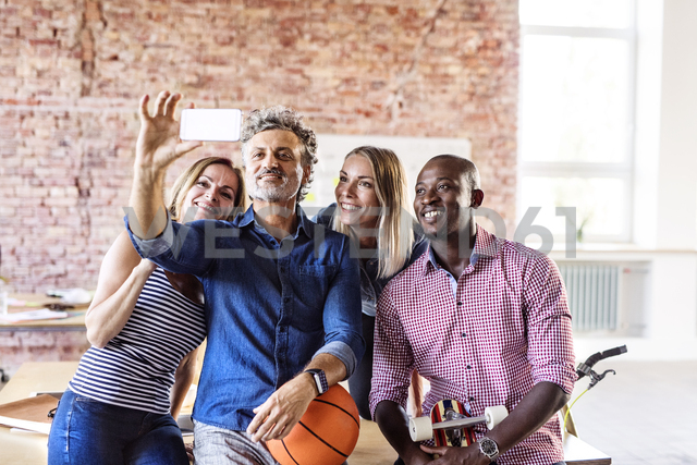 Happy colleagues with basketball in office taking a selfie - HAPF02632