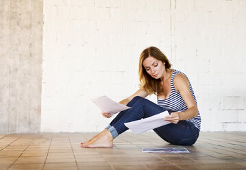 Woman sitting on the floor reviewing paper - HAPF02650