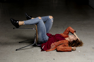 Laughing woman lying on the floor with chair - HHLMF00003