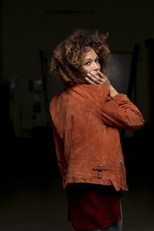 Portrait of woman wearing leather jacket in front of dark background - HHLMF00006