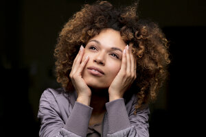 Portrait of daydreaming woman in front of black background - HHLMF00009
