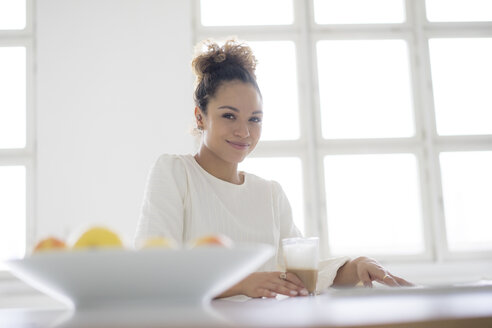 Portrait of smiling young woman sitting at table with glass of coffee - HHLMF00033