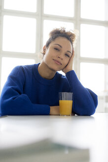 Portrait of smiling young woman  with glass of orange juice at table - HHLMF00039