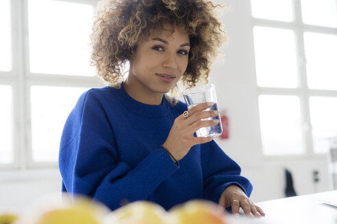 Portrait of smiling young woman drinking glass of water at table - HHLMF00042