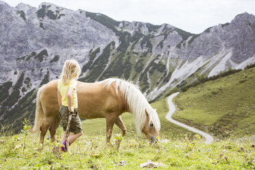 Austria, South Tyrol, young girl with horse on meadow - FKF02865
