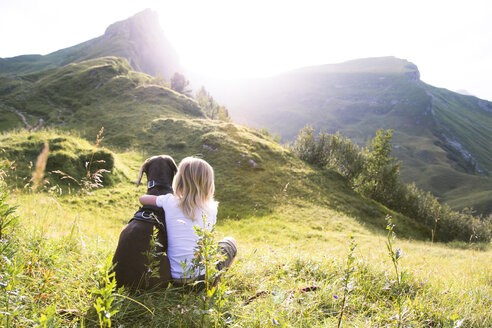 Austria, South Tyrol, young girl sitting with dog on meadow - FKF02874