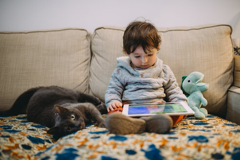 Baby girl sitting on couch watching videos on a tablet with a cat - GEMF01833