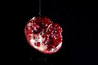Sliced pomegranate in front of black background - JTF00880
