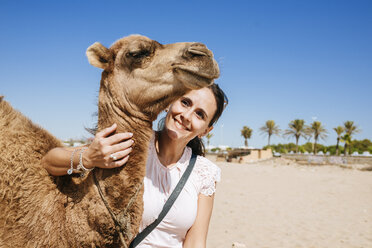 Morocco, Tanger, portrait of smiling woman with baby camel on the beach - KIJF01798