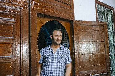 Morocco, portrait of tourist standing in typical arabic door frame - KIJF01801
