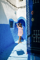 Morocco, Chefchaouen, woman standing in front of blue door enjoying sunlight - KIJF01807