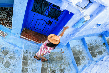 Morocco, Chefchaouen, woman walking alley downwards, top view - KIJF01810