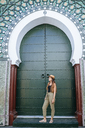 Morocco, Chefchaouen, woman standing in front of green portal - KIJF01813