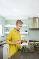 Smiling young woman preparing salad in kitchen - MFRF01065