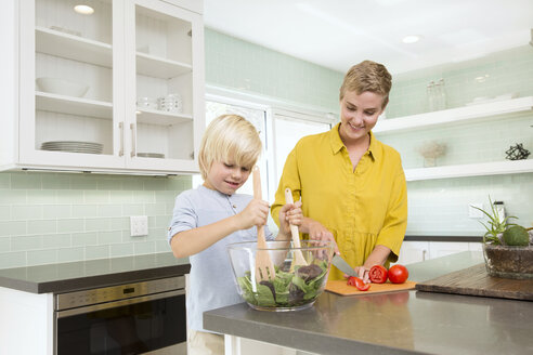 Smiling mother and son preparing salad in kitchen together - MFRF01068