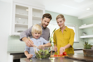 Smiling family preparing salad in kitchen together - MFRF01071