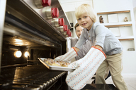 Smiling boy taking baking tray out of the oven with father in background - MFRF01074