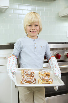 Portrait of smiling boy holding baking tray with cinammon buns - MFRF01077