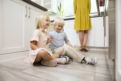 Brother and sister sitting on the floor in kitchen looking at oven - MFRF01080