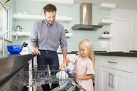 Girl helping father clearing the dishwasher in kitchen - MFRF01083