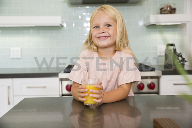 Portrait of smiling girl in kitchen with glass of orange juice - MFRF01086