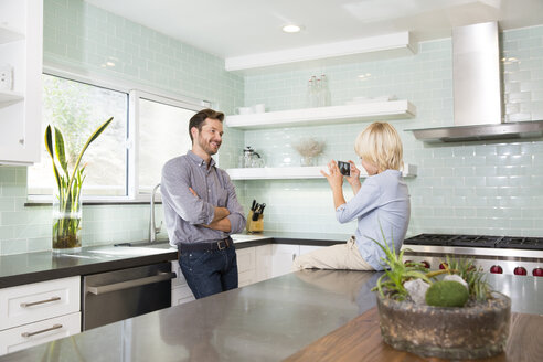 Son taking cell phone picture of father in kitchen - MFRF01092