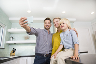 Father taking selfie with his family in kitchen - MFRF01095