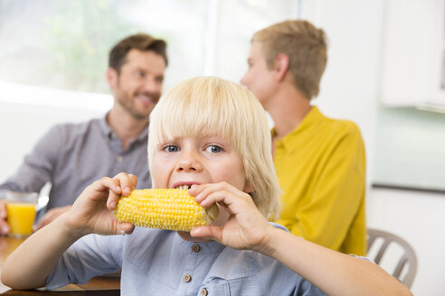 Boy eating corn cob in kitchen with parents in background - MFRF01098