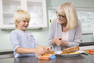 Grandmother and grandson preparing lunch box in kitchen together - MFRF01101