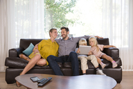 Family sitting on couch at home using tablet - MFRF01104