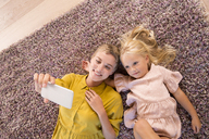 Smiling mother and daughter lying on carpet taking a selfie - MFRF01110