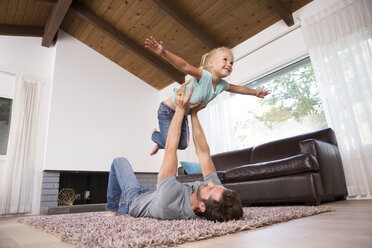 Father playing with daughter on carpet in living room at home - MFRF01113